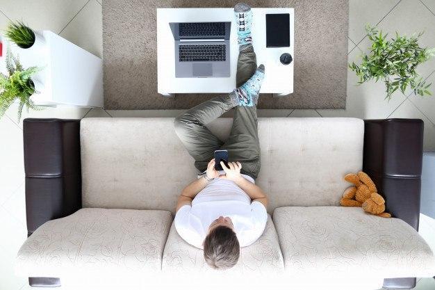 Hombre en salón de su casa controlando su calefacción por una app